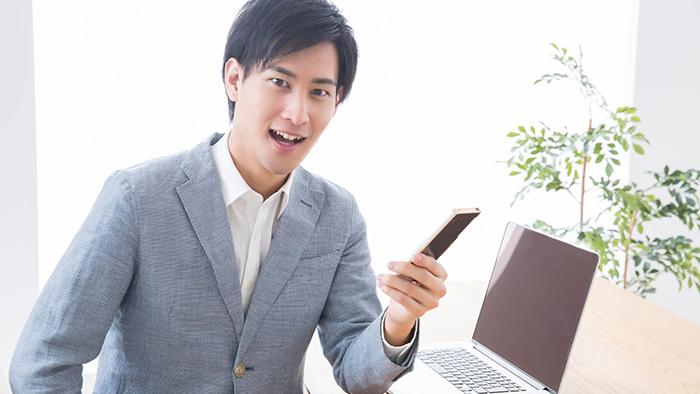 ノートパソコンの前でスマホを持っている男性