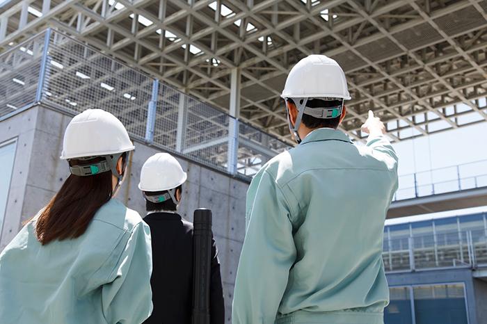 工事現場を確認している作業着の男女
